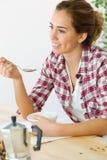 Belle jeune femme appréciant le petit déjeuner dans sa nouvelle maison Photos libres de droits