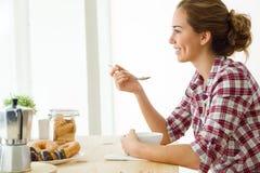 Belle jeune femme appréciant le petit déjeuner dans sa nouvelle maison Images libres de droits