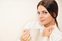 Belle jeune femme appréciant une tasse de café tout en détendant à la maison Photo stock