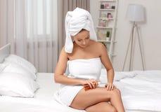 Belle jeune femme après le bain appliquant des sécrétions cutanées sur la peau Image stock