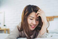 Belle jeune femme asiatique de portrait sur le lit à la maison pendant le matin photographie stock libre de droits
