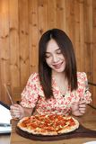 Belle jeune femme asiatique mangeant de la pizza délicieuse ou délicieuse photo stock