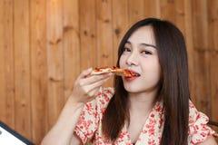 Belle jeune femme asiatique mangeant de la pizza délicieuse ou délicieuse image libre de droits