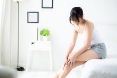 Belle jeune femme asiatique s'asseyant sur un lit frottant des jambes avec la peau lisse molle dans la chambre à coucher image stock