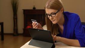 Belle jeune femme attirante se trouvant sur le sofa et achetant quelque chose en ligne avec la carte de crédit 00329 banque de vidéos
