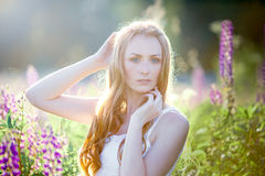 Belle jeune femme au-dessus des lupines de floraison Photo libre de droits
