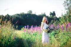 Belle jeune femme au-dessus des lupines de floraison avec le groupe de fleurs dans des mains Photos libres de droits