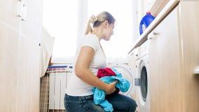 Belle jeune femme au foyer prenant des vêtements hors de la machine à laver dans la blanchisserie photographie stock libre de droits
