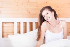 Belle jeune femme aux cheveux longs heureuse se réveillant pendant le matin et s'étirant dans le lit à la maison Photo libre de droits