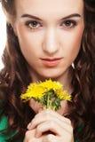 Belle jeune femme avec de grands pissenlits jaunes Image stock