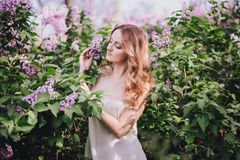 Belle jeune femme avec de longs cheveux bouclés dans un jardin avec des lilas Photographie stock libre de droits