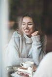 Belle jeune femme avec de longs cheveux bruns se reposant en café, drin Image libre de droits