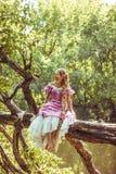 Belle jeune femme avec de longs cheveux, tordus dans une tresse, dans la robe rose se reposant sur l'arbre luxuriant Photographie stock