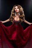Belle jeune femme avec de longs cheveux volumineux onduleux, maquillage lumineux, rouge à lèvres rouge, boucles d'oreille blanche photo libre de droits