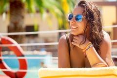 Belle jeune femme avec des lunettes de soleil détendant par la piscine Image libre de droits