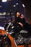 Belle jeune femme avec des lunettes de soleil parlant au téléphone et se penchant sur sa moto la nuit Image stock