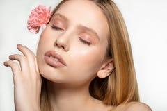 Belle jeune femme avec des yeux ferm?s, peau parfaite avec la fleur rose courb?e dans les cheveux, se tenir, touchant le visage a images libres de droits