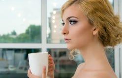 Belle jeune femme avec l'avant de tasse de la fenêtre Images libres de droits
