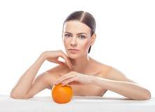 Belle jeune femme avec l'orange d'isolement sur le fond blanc Photographie stock