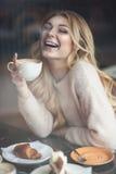 Belle jeune femme avec la longue tasse blonde de boissons de cheveux de coff Photographie stock