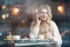 Belle jeune femme avec la longue tasse blonde de boissons de cheveux de coff Image stock