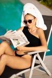 Belle jeune femme avec la serviette sur son journal de lecture de cheveux près de piscine d'hôtel photos stock