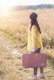 Belle jeune femme avec la valise brune de vintage et le chapeau noir dans la route de champ pendant le coucher du soleil d'été photo libre de droits