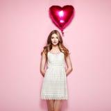 Belle jeune femme avec le ballon à air de forme de coeur Image stock
