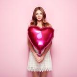 Belle jeune femme avec le ballon à air de forme de coeur Photographie stock libre de droits