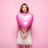 Belle jeune femme avec le ballon à air de forme de coeur Images stock