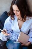 Belle jeune femme avec le carnet de programme de téléphone portable dans l'intérieur à la maison élégant Indépendant dans son lie Image libre de droits