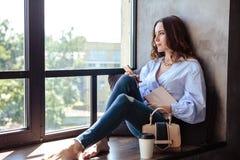 Belle jeune femme avec le carnet de programme de téléphone portable dans l'intérieur à la maison élégant Indépendant dans son lie Photos stock