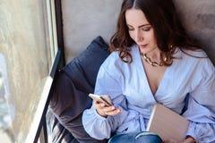 Belle jeune femme avec le carnet de programme de téléphone portable dans l'intérieur à la maison élégant Indépendant dans son lie Image stock
