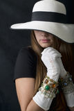 Belle jeune femme avec le chapeau souple élégant, les gants de long vintage et les bijoux blancs Photographie stock libre de droits