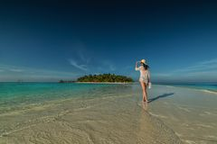 Belle jeune femme avec le chapeau sur la plage blanche, beau paysage avec la femme en Maldives, paradis tropical photographie stock libre de droits