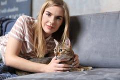 Belle jeune femme avec le chat mignon sur la maison de sofa Photos stock