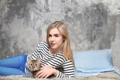 Belle jeune femme avec le chat mignon sur le lit Photos libres de droits