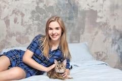 Belle jeune femme avec le chat mignon sur le lit Photo stock