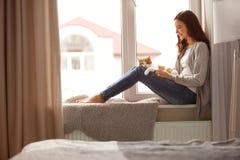 Belle jeune femme avec le chat mignon sur le rebord de fenêtre Photos libres de droits