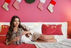 Belle jeune femme avec le chat se trouvant sur le lit à la maison Photographie stock