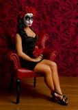 Belle jeune femme avec le crâne de sucre entouré par le rouge Photographie stock libre de droits