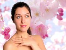 Belle jeune femme avec le fond de fleur de ressort photo stock