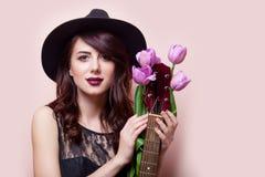 Belle jeune femme avec le groupe de tulipes et de guitare sur gagné Images stock