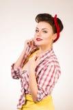 Belle jeune femme avec le renivellement et la coiffure de broche-vers le haut posant au-dessus du fond rose Image stock