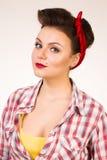 Belle jeune femme avec le renivellement et la coiffure de broche-vers le haut posant au-dessus du fond rose Images libres de droits