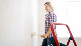 Belle jeune femme avec le rouleau de peinture faisant la rénovation à la nouvelle maison photographie stock