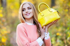Belle jeune femme avec le sac à la mode jaune dans des mains sur la nature d'automne Images stock