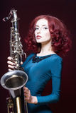 Belle jeune femme avec le saxo photographie stock libre de droits