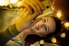 Belle jeune femme avec le téléphone sur un fond des lampes-torches Photographie stock libre de droits