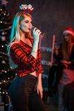 Belle jeune femme avec le verre de champagne à la fête de Noël Photos libres de droits